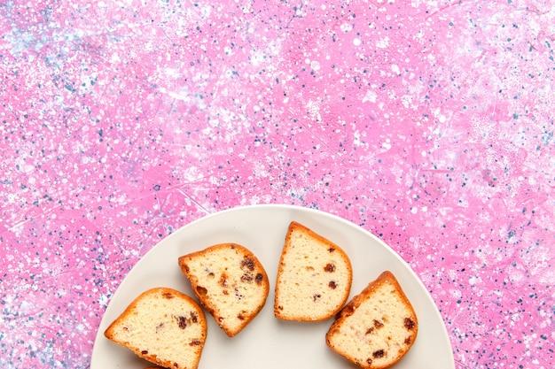 Vista superior de las rebanadas de pastel con pasas dentro de la placa sobre fondo rosa pastel hornear galletas dulces de azúcar de color