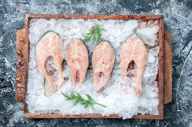 Vista superior rebanadas de pescado crudo con hielo en tablero de madera en la mesa
