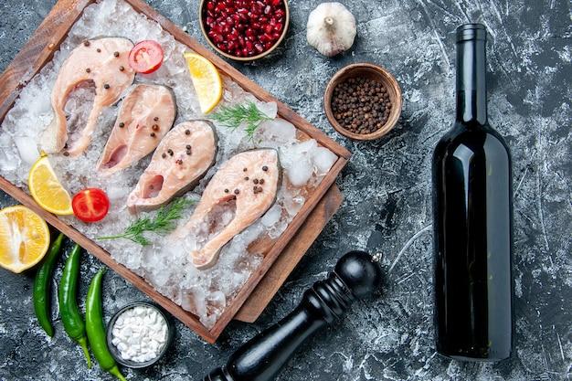 Vista superior de las rebanadas de pescado crudo con rodajas de limón helado en una botella de vino de tablero de madera en la mesa