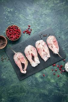 Vista superior rebanadas de pescado fresco en la mesa oscura carne mariscos comida de mar plato agua cruda comida pimienta del océano