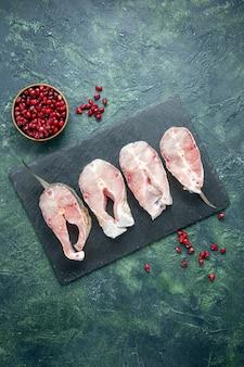 Vista superior de las rebanadas de pescado fresco en la mesa oscura, carne, mariscos, mar, comida de mar, plato, agua cruda