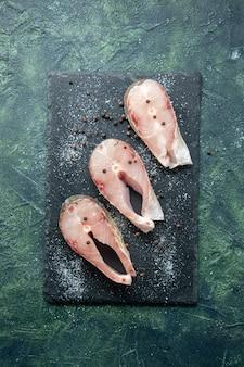 Vista superior rebanadas de pescado fresco en la mesa oscura mariscos carne de mar comida de mar plato comida ensalada agua pimienta