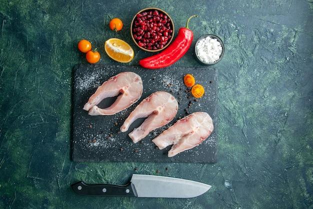 Vista superior rebanadas de pescado fresco en la mesa oscura mariscos carne de mar comida de mar plato ensalada agua pimienta comida