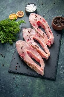 Vista superior rebanadas de pescado fresco con pimienta en superficie oscura carne agua cruda foto color cena comida del océano mariscos