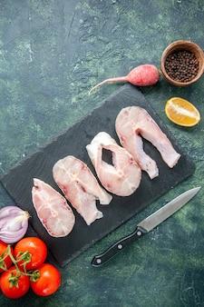 Vista superior rebanadas de pescado fresco con tomates rojos en una mesa azul oscuro carne de mar comida de marisco plato de agua de pimienta comida de mar