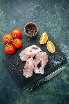 Vista superior rebanadas de pescado fresco con tomates rojos en una mesa azul oscuro carne de mar mariscos comida de mar comida pimienta plato de agua