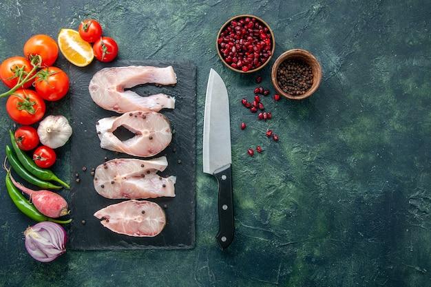 Vista superior rebanadas de pescado fresco con tomates rojos sobre fondo oscuro carne de mar comida de mar comida de agua plato de pimienta mariscos