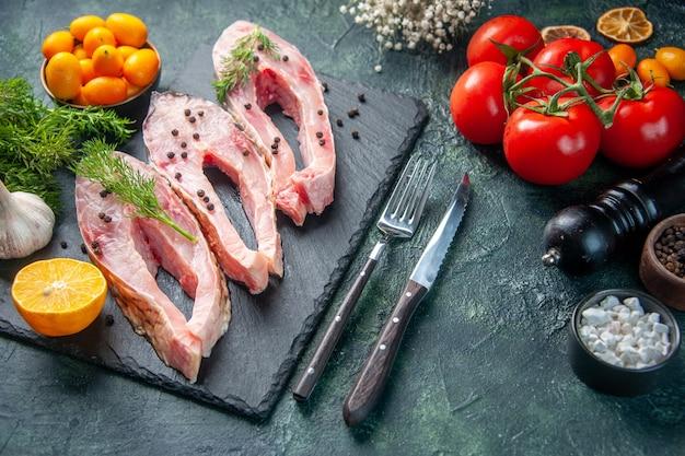 Vista superior rebanadas de pescado fresco con verduras tomates y kumquats en la superficie oscura carne del océano foto cruda marisco color cena agua comida