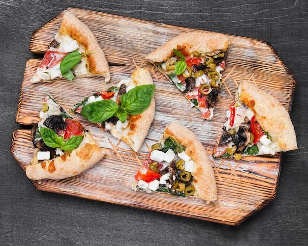 Vista superior rebanadas de pizza en tabla de cortar