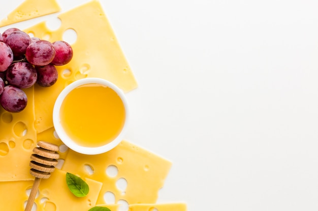 Vista superior rebanadas de queso emmental uvas y miel con espacio de copia