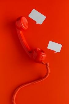 Vista superior del receptor de teléfono con cable y burbujas de chat