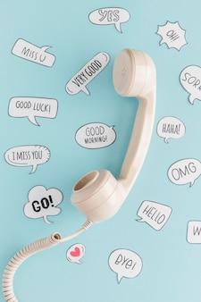 Vista superior del receptor de teléfono retro con burbujas de chat
