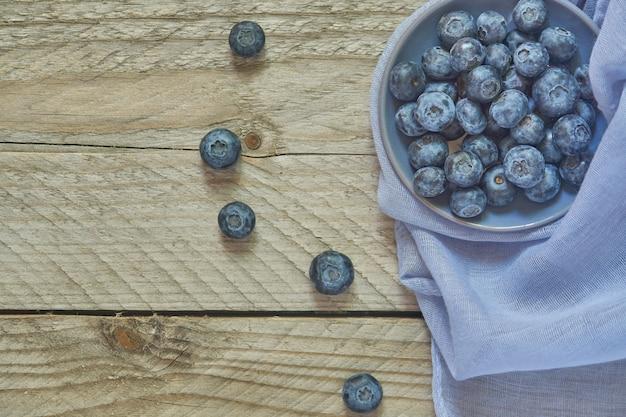 Vista superior del recipiente con arándanos en la mesa de madera y textil azul.
