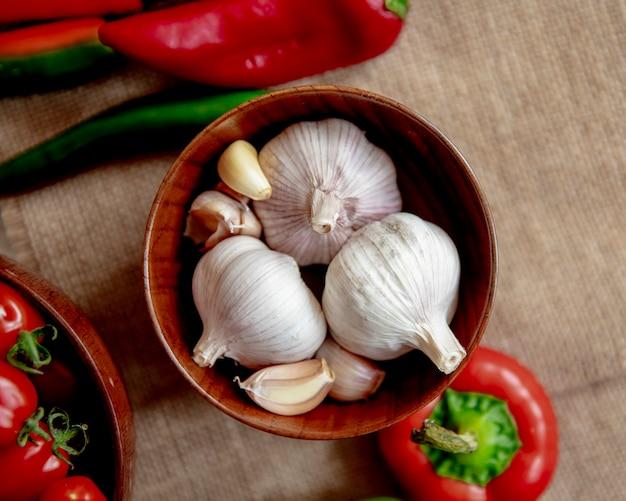 Vista superior del recipiente lleno de ajo con otras verduras en la superficie de tela de saco
