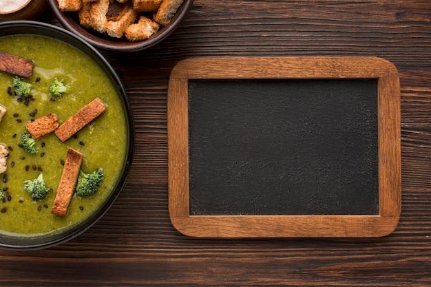 Vista superior del recipiente con sopa de brócoli de invierno y pizarra