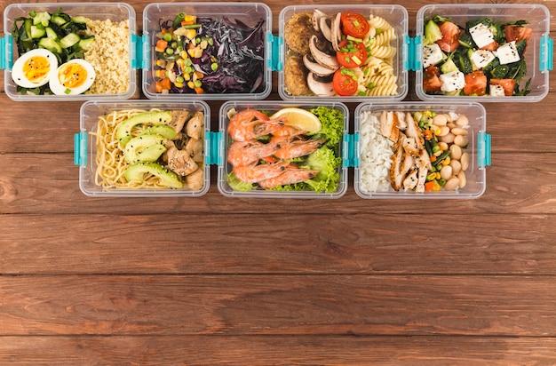 Vista superior de recipientes organizados de plástico con alimentos.