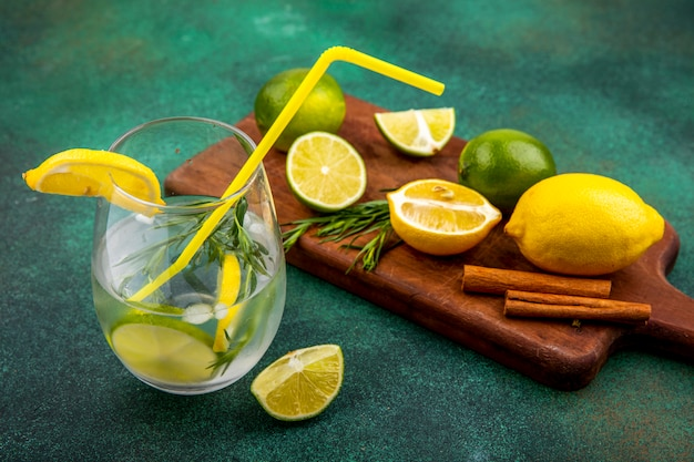 Vista superior de refrescante agua de desintoxicación en un vaso con limones y lima sobre una tabla de cocina de madera con palitos de canela en la superficie verde