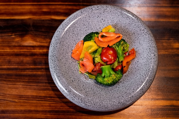 Vista superior de la refrescante ensalada con salmón en un hermoso plato gris en el mostrador de madera