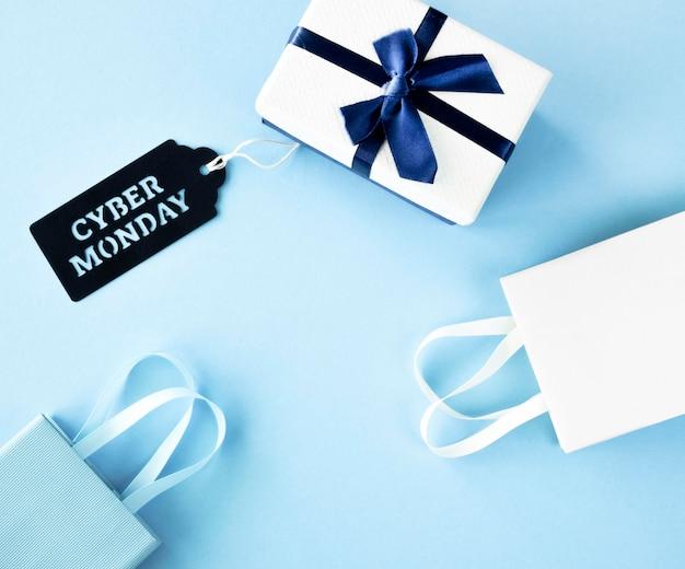 Vista superior del regalo con bolsas de compras y etiqueta para cyber monday