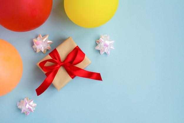 Vista superior del regalo con lazo rojo y globos de colores en el azul