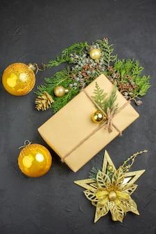 Vista superior regalo de navidad ramas de abeto juguetes de árbol de navidad en superficie beige