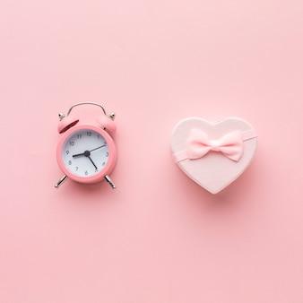 Vista superior de regalo rosa con reloj