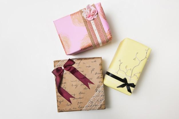 Vista superior de regalos envueltos festivos sobre fondo blanco. concepto de felicitaciones, regalos y saludos