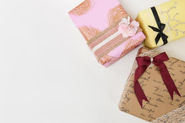 Vista superior de regalos envueltos festivos sobre fondo blanco con espacio libre a la izquierda. concepto de felicitaciones, regalos y saludos