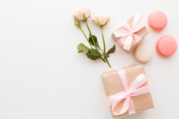 Vista superior de regalos con macarons y rosas