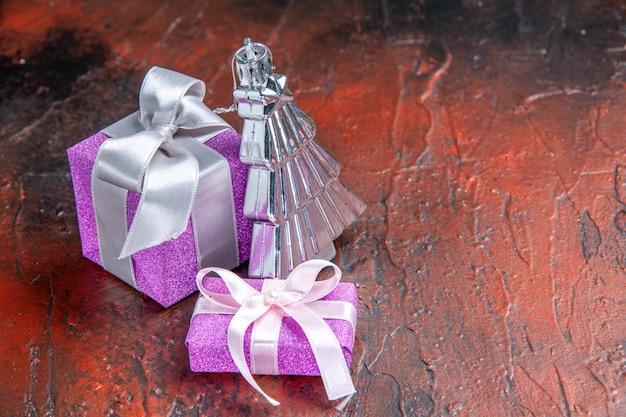 Vista superior de regalos de navidad con caja rosa y cinta blanca, juguete de árbol de navidad sobre fondo rojo inglés