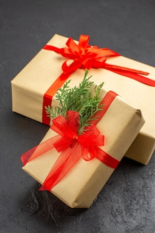 Vista superior de regalos de navidad grandes y pequeños en papel marrón atado con cinta roja sobre una superficie oscura