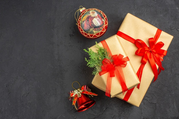 Vista superior de regalos de navidad grandes y pequeños en papel marrón atado con juguetes de árbol de navidad de cinta roja sobre fondo oscuro