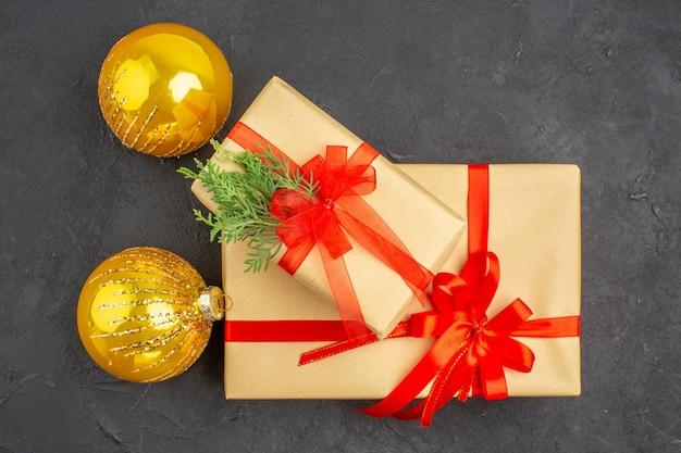 Vista superior de regalos de navidad grandes y pequeños en papel marrón atados con bolas de navidad de abeto de rama de cinta roja sobre superficie oscura