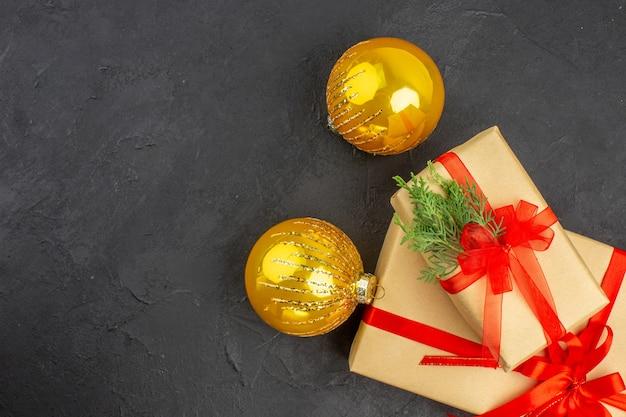 Vista superior de regalos de navidad grandes y pequeños en papel marrón atados con bolas de navidad de cinta roja sobre una superficie oscura