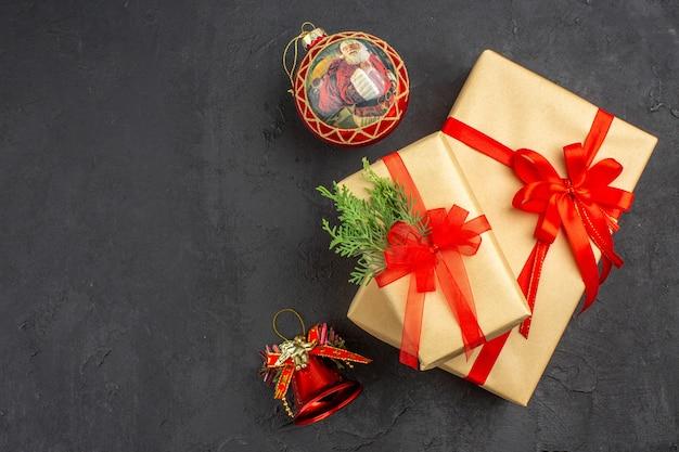 Vista superior de regalos de navidad grandes y pequeños en papel marrón atados con cinta roja juguetes de árbol de navidad en superficie oscura
