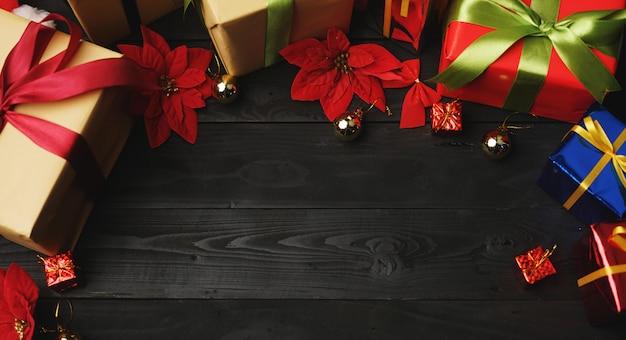 Vista superior de regalos de navidad en madera negra. espacio para texto