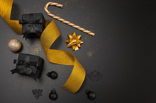 Vista superior de regalos de navidad oscuros con cinta dorada