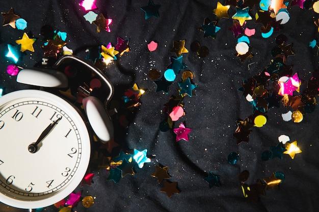 Vista superior del reloj y confeti de colores