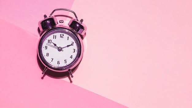 Vista superior reloj sobre fondo rosa