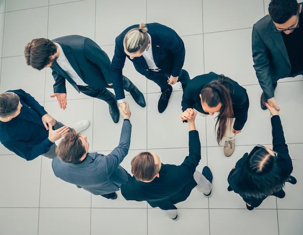 Vista superior. los representantes de los equipos empresariales se saludan con un apretón de manos.