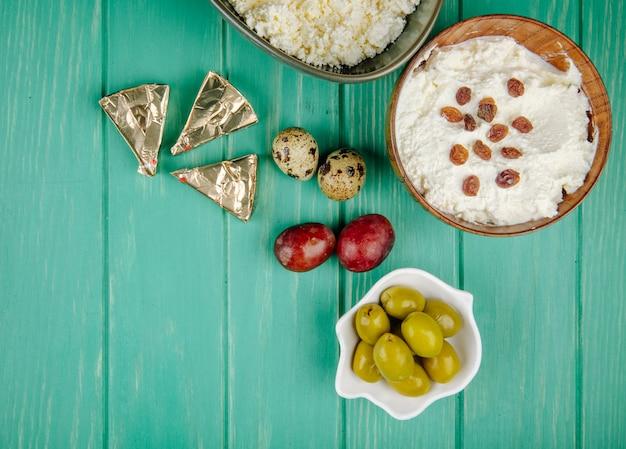 Vista superior de requesón con pasas en un tazón de madera con triángulos de queso crema y aceitunas en vinagre, huevos de codorniz y uvas dulces en madera verde