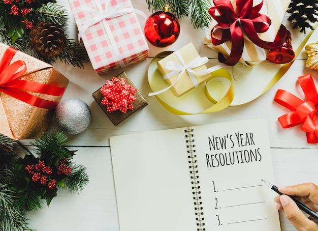 Vista superior de las resoluciones de año nuevo en el cuaderno y la caja de regalo de navidad y año nuevo.