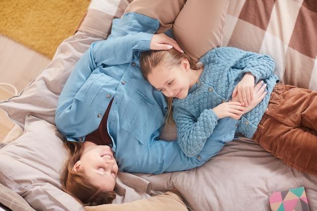 Vista superior retrato de madre feliz abrazando a linda chica y sonriendo el uno al otro mientras está acostado en la cama en casa, espacio de copia