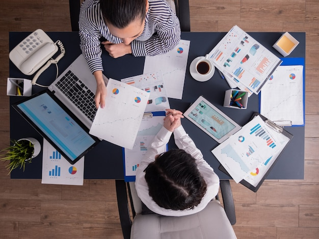 Vista superior de la reunión de trabajadores de oficina analizando gráficos financieros con portapapeles