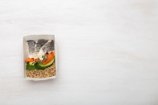 Vista superior de rodajas de calabacín pescado y gachas de trigo junto a rodajas de puerro y zanahoria y condimentos. concepto de alimentación saludable, espacio de copia