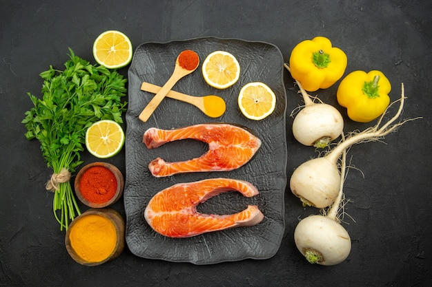 Vista superior de rodajas de carne fresca con verduras de limón y condimentos sobre fondo oscuro