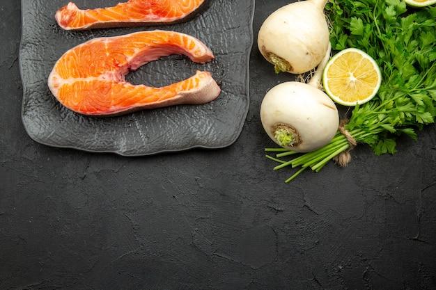 Vista superior de rodajas de carne fresca con verduras y limón sobre fondo oscuro