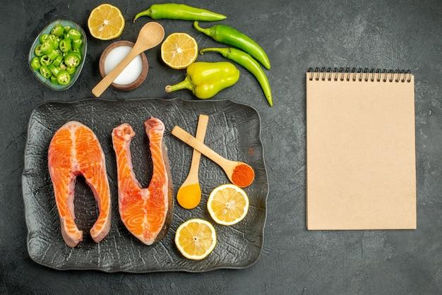 Vista superior de rodajas de carne frita con pimientos y limón sobre el fondo oscuro