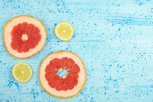 Vista superior rodajas de cítricos pomelos y limones en el piso azul brillante