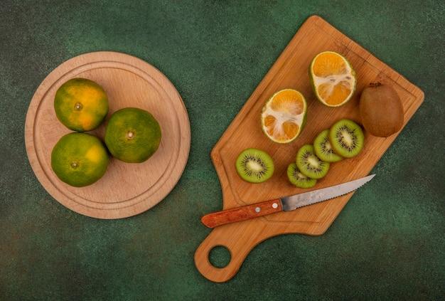 Vista superior de rodajas de kiwi con un cuchillo sobre una tabla de cortar con mandarinas en un soporte sobre una pared verde